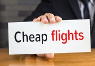 Cheap flights, message on white card and hold by businessman